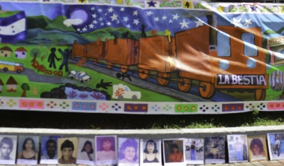 Honduras, Tegucigalpa, Central Park. A pedestrian is looking at portraits of missing persons during the International Day of Missing Persons. Returned migrants and relatives of the missing painted a moveable mural.