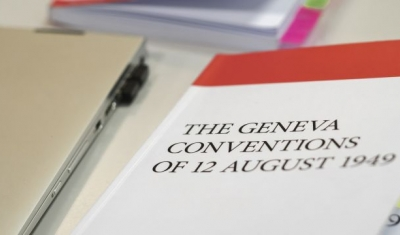 A labtop and the book of the 1949 Geneva Conventions