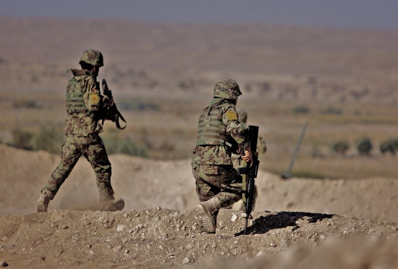 Soldiers from the 2nd Brigade, 215th Corps respond to a Taliban attack from the valley below Combat Outpost Nolay in Sangin, Helmand province.